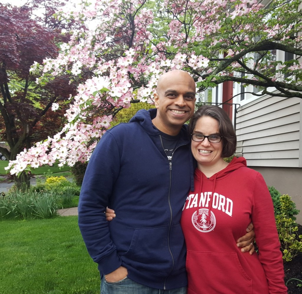Brian in a blue sweatshirt and Karen in a Stanford red sweatshirt standing in front of a pink dogwood tree.